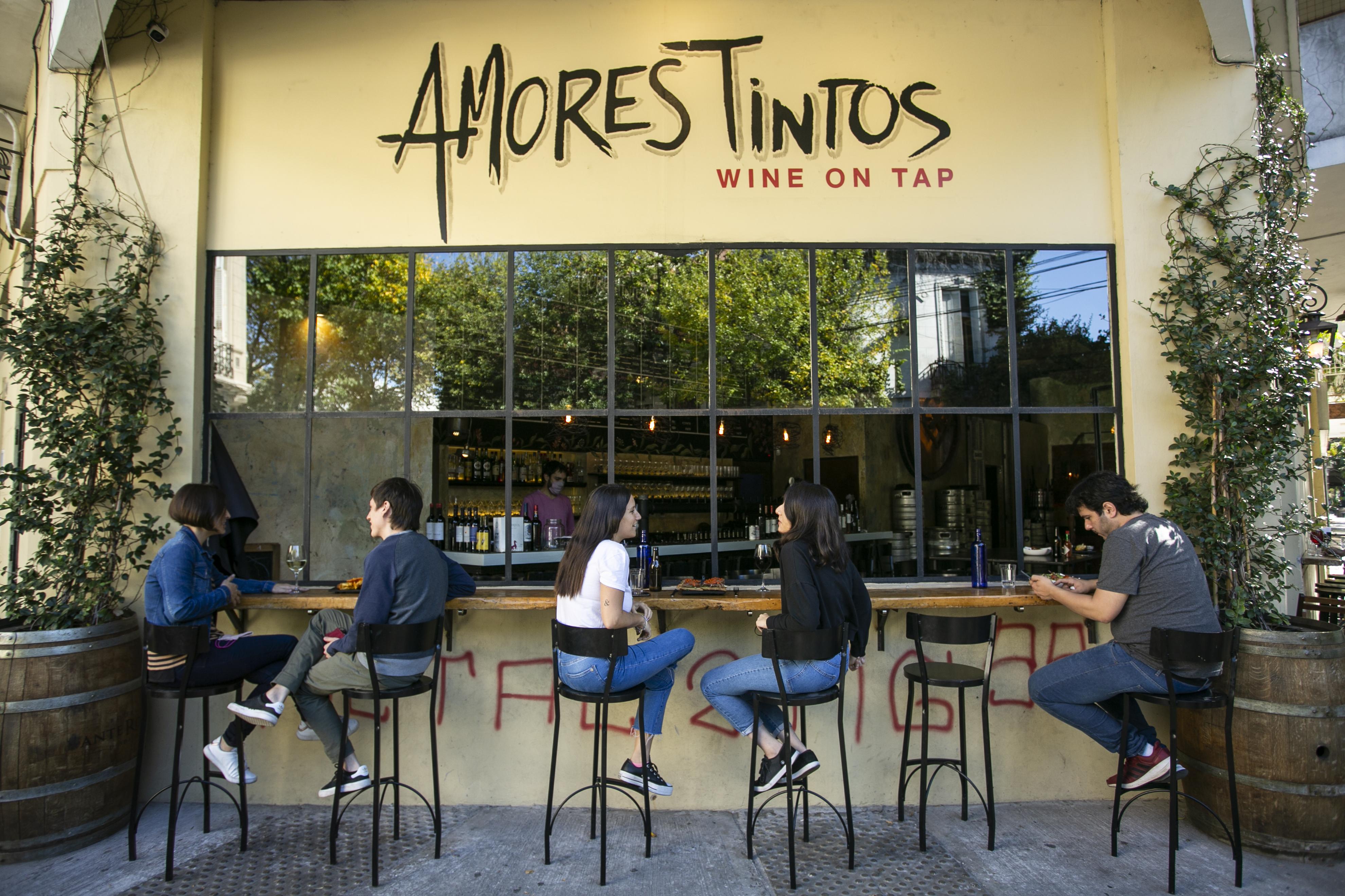 cuatro personas sentadas en la vereda del wine bar y charlando.